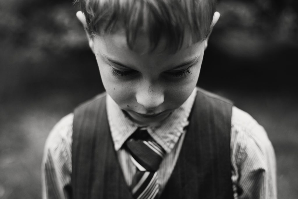 Boy in dress vest, shirt and tie alone and sad.